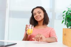 Pretty mulatto woman with juice Stock Photos