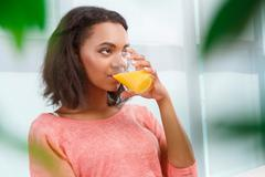 Pretty mulatto woman drinking orange juice - stock photo