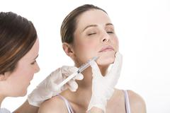 Doctor doing  botox injection to a woman Stock Photos