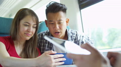 4k Happy mixed ethnicity group of friends using technology on train journey Stock Footage
