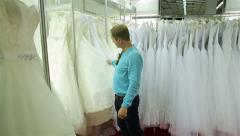 The young man puzzled looks at the dresses in the Bridal salon. Stock Footage