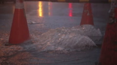 Overflowing manhole in storm with warning beacons slow motion MCU Stock Footage