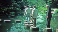 1972: People walking the stepping stones around the zen Japanese style pond. - stock footage