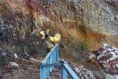 Stock Photo of worker carry sulfur for selling at Kawah Ijen