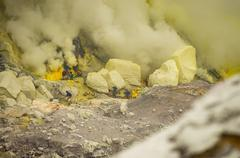 worker carry sulfur for selling at Kawah Ijen - stock photo