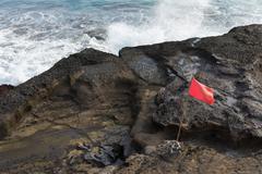 water break sea wave coast rock border red flag - stock photo