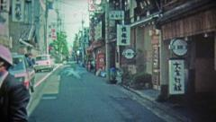 1972: Japanese wooden tourist items and city street. Stock Footage