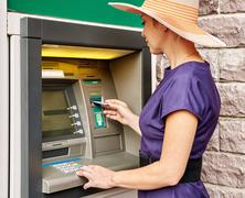 Pretty woman operates ATM - stock photo