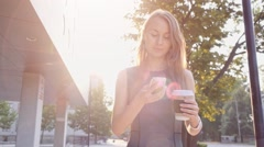 Attractive business woman walking in the city, drinking coffee and using a Stock Footage