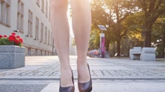 Woman legs in heeled shoes crossing the road. Steadicam stabilized, Slow-mo. Stock Footage