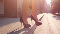 Sexy businesswoman in black high-heeled shoes is walking down the stairs in the Stock Footage