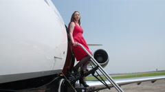 Woman in red dress smiles from the stairs of a business jet 4K Stock Footage