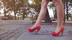 Woman walking in red high heeled shoes and stopping to massage her tired leg. Stock Footage