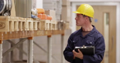 Warehouse manager inspecting stock levels in a manufacturing plant. - stock footage