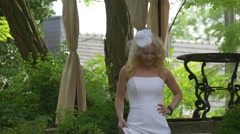 Blonde Woman in Modern White Sheath Wedding Dress Small White Hat with Veil - stock footage