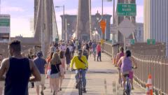 Crowd Brooklyn Bridge people walking crowded bicycles New York City NYC sunny - stock footage