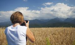 Traveler girl photographing ripe wheat field in bright sun rays - stock photo