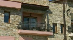 Establishing shot of balcony on private stone house, summertime, sunny weather Stock Footage