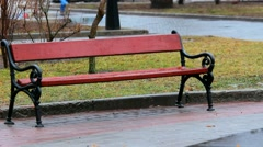 Bench at city park on rainy cold day Stock Footage
