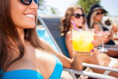 Attractive young friendly girls are getting a suntan - stock photo