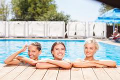Cheerful young girls are swimming in blue water Stock Photos