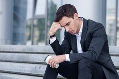 Attractive young businessman is worrying about his job Stock Photos