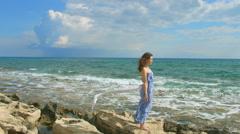 Happy woman standing on rocky beach, enjoying ocean breeze, waves coming ashore - stock footage
