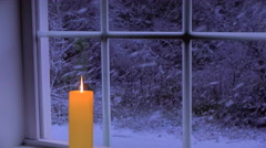 Golden candle by window.  Snowing outside.  Dusk. Stock Footage