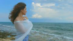 Horizontal panorama of beautiful lonely woman on sea shore, hair waving in wind Stock Footage