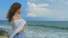 Lonely woman on beach, white scarf wrapped around her body. Marine landscape Stock Footage