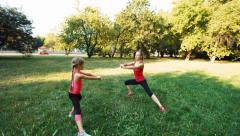Family mother with daughter doing fitness in the park. Camera flying around 1 Stock Footage