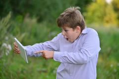 Teen boy with  tablet computer at nature - stock photo