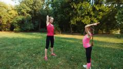 Athlete family mother and daughter doing fitness in the park Stock Footage