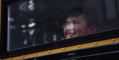 Wide shot of Young asian boy excited about school on on school bus Stock Footage