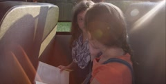 Stock Video Footage of Two little girls reading on school bus