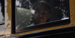 Sad black girl looking in window of school bus - stock footage