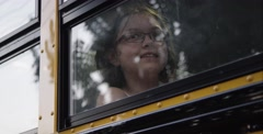 Nerdy girl with goofy smile in a school bus window - stock footage