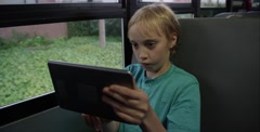 Stock Video Footage of Girl stealing boys iPad on school bus