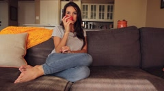 Attractive woman on couch eating tomato wide shot Stock Footage