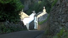 Man walking downhill through Castleton village, Peak District. - stock footage