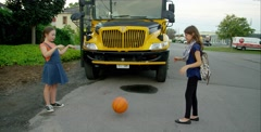 Girls passing a basketball in front of a school bus - stock footage