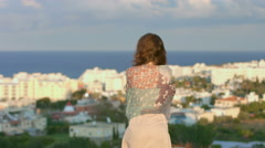 Sad woman wrapped in scarf looks at seaside town, amazing landscape, magic hour Stock Footage