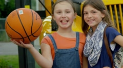 Cute young girls posing with basketball in front of school bus - stock footage