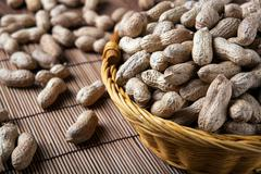 large grains of peanuts in the shell and basket - stock photo