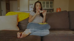 Attractive woman on couch takes bite of banana from hand wide shot Stock Footage