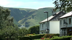 Houses with hill backdrop, Castleton, Peak District. - stock footage