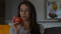 Attractive woman on couch inspects big red tomato in hand Stock Footage