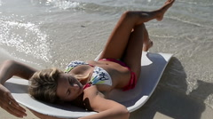 Rotating shot around sunbathing woman on tropical beach - stock footage