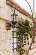 Stone fence with wrought-iron grille Stock Photos