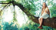 Child girl 6-8 years blowing soap bubbles and sitting on a tree Stock Footage